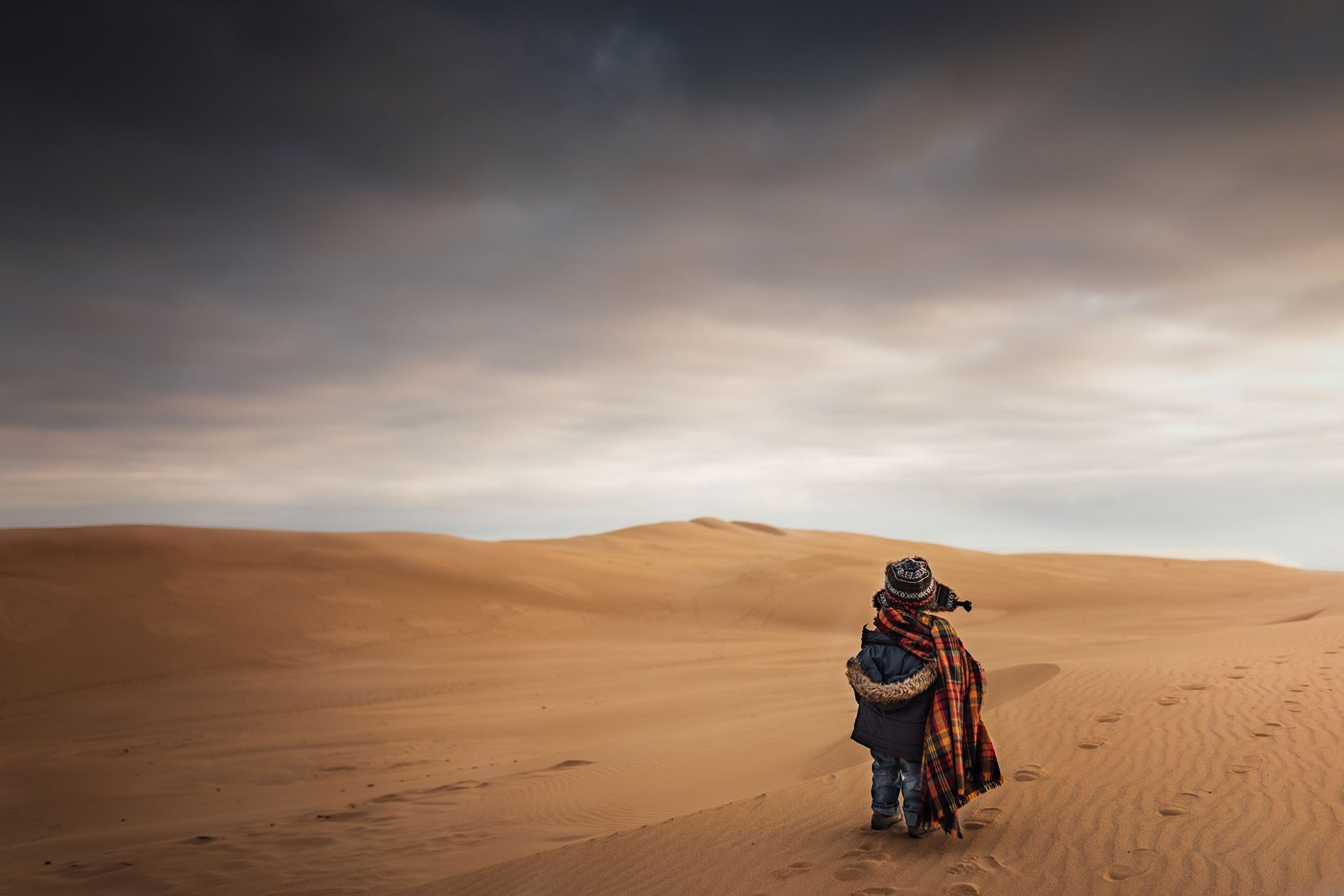 photo of boy dressed warm standing on sand by Megan Loeks