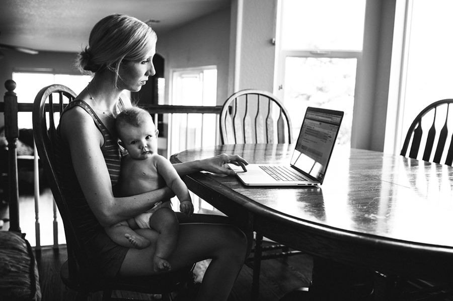 baby on moms lap while working photo