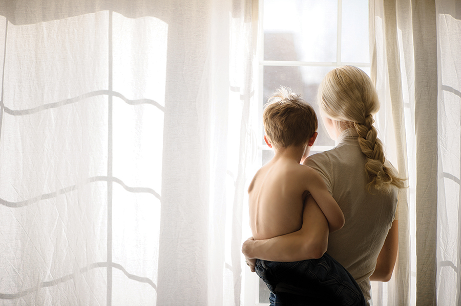 mom holding son looking out window photo by Sarah Wilkerson