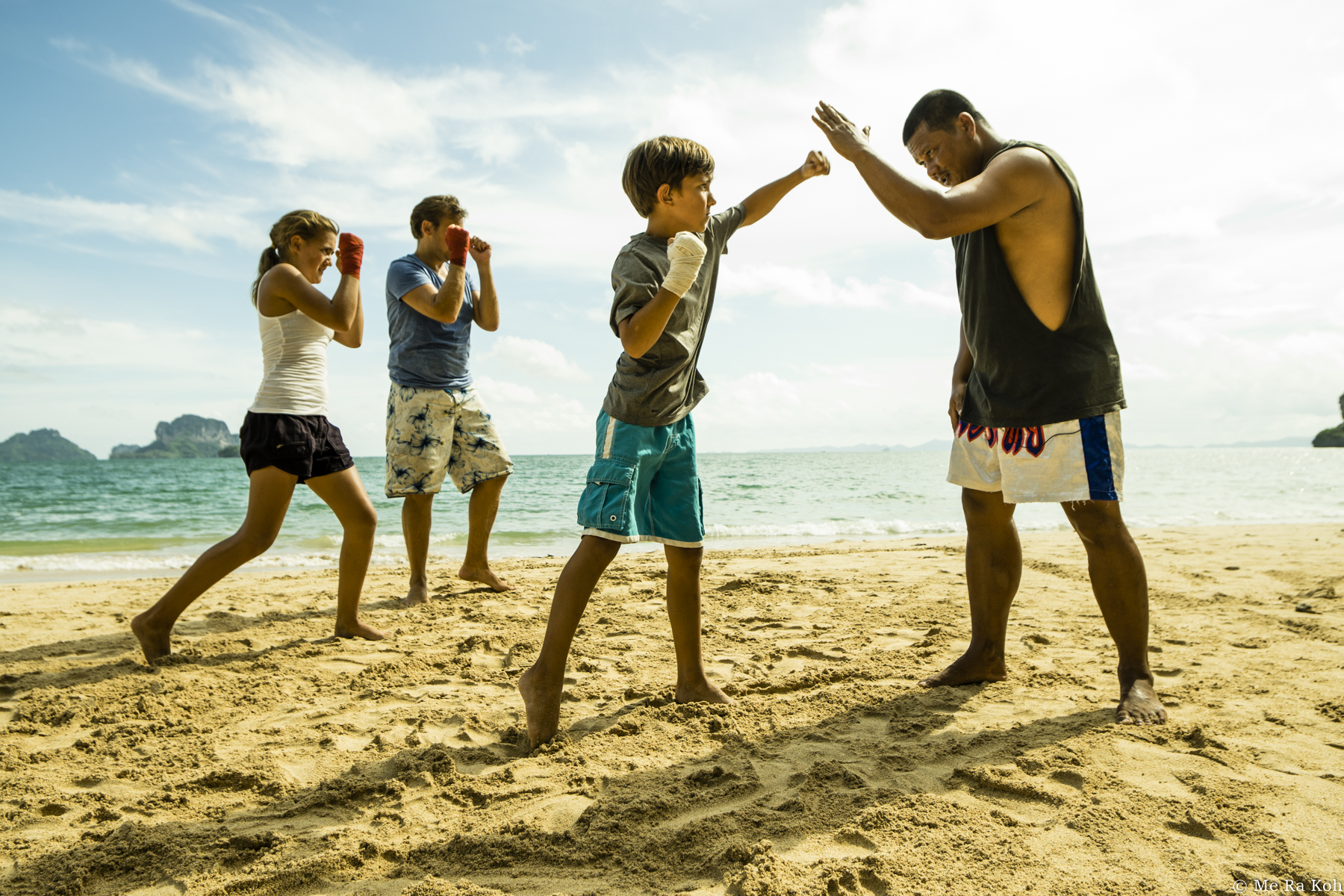 photo of people boxing on the beach by Me Ra Koh