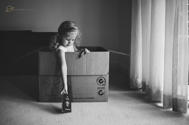 girl playing in an empty box by Emma Wood