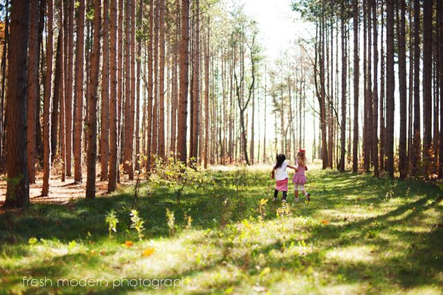children running in field with trees photograph by Micki DeVries