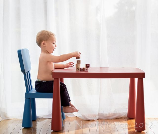 child sitting at play table photograph by Nina Mingioni