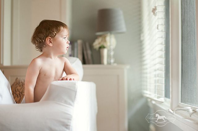 child sitting on couch looking out window photograph by Rebecca Bixler
