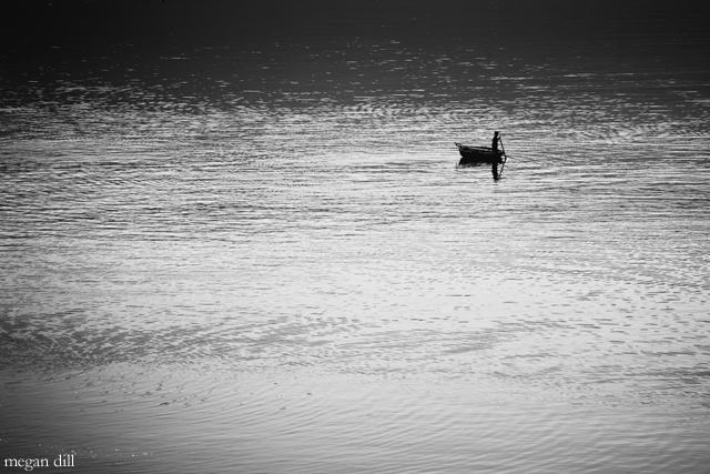 small boat and fisherman on large lake by Megan Dill