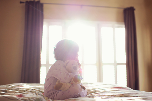 backlit photo of girl sitting on bed by Melissa Gibson