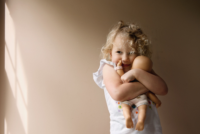 girl hugging her baby doll by Meredith Novario