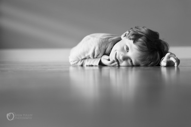 child laying on ground by Julia Tulley