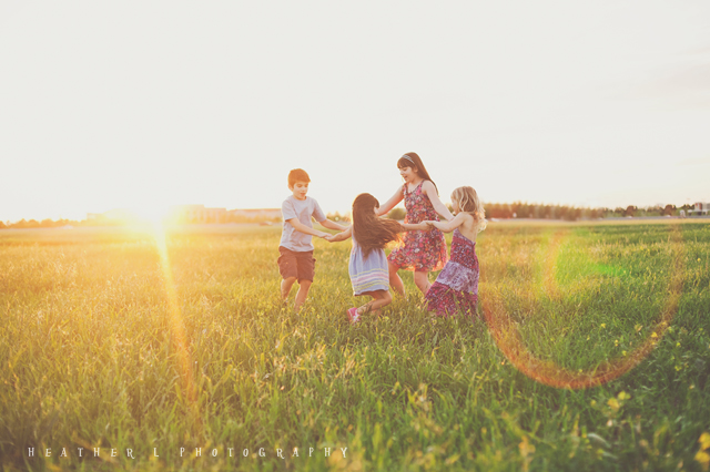 kids twirling in a field at sunset by Heather Lazark