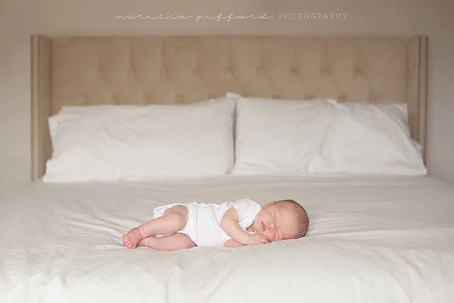 newborn photo on parents bed by Marissa Gifford