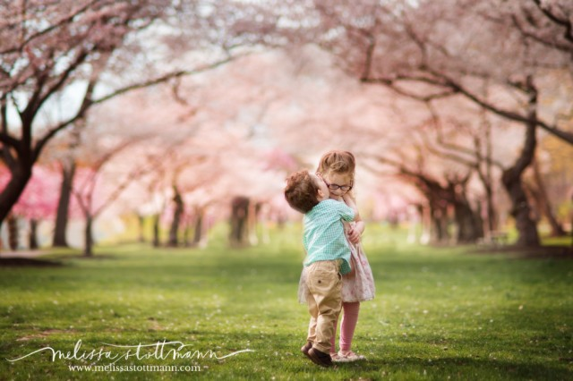 siblings in front of cherry blossoms photo by Melissa Stottmann