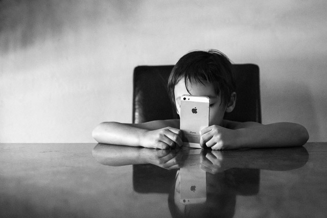 boy playing on iPhone by amcarlon