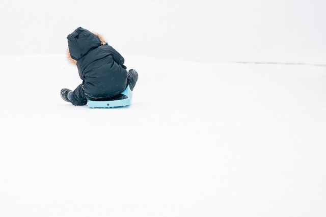 child sledding in snow photo by Sarah Lalone