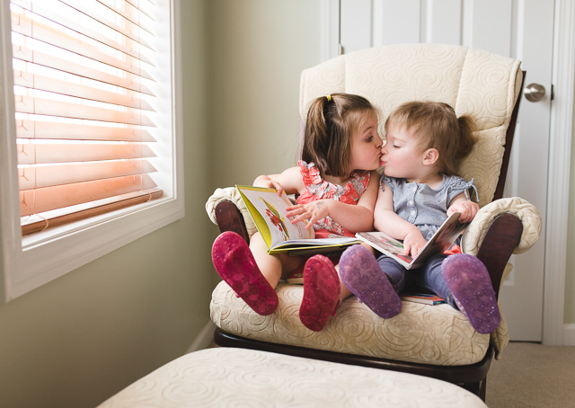 siblings reading books in a chair photo by Kristy Dooley