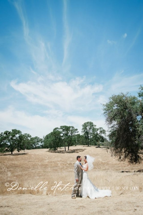 bride and groom portrait in a field by Danielle Hatcher