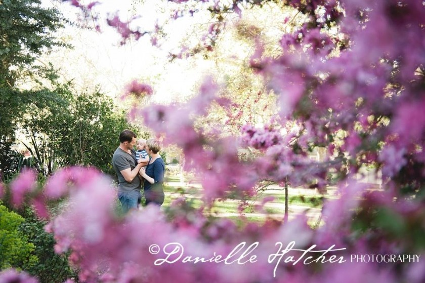 family photographed through pretty purple flower tree by Danielle Hatcher