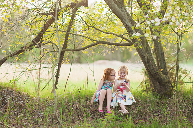 girls sitting under tree in a field photo