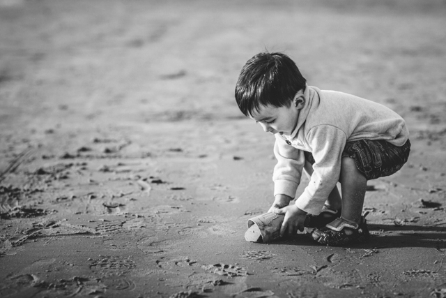 kid digging up sand on the beach picture