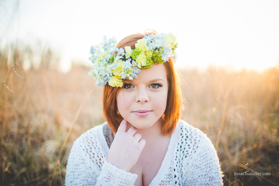 backlit portrait of senior wearing a flower crown by Lissa Chandler