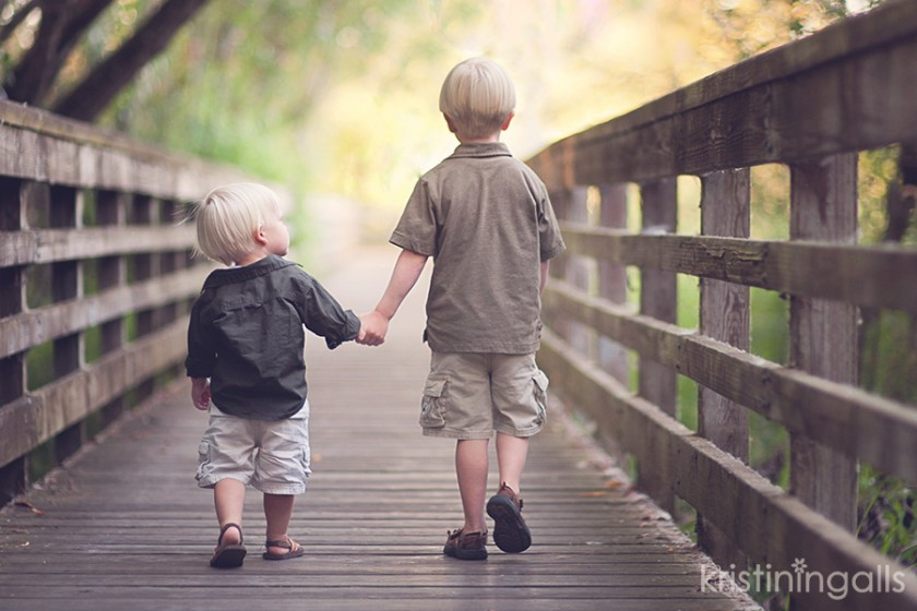brothers holding hands walking down a bridge pic by Kristin Ingalls