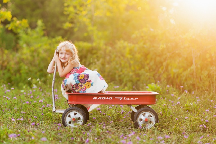 girl riding in red wagon photo by Mickie DeVries
