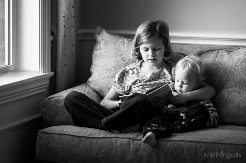 siblings sitting on the couch reading a book picture by Kristin Ingalls