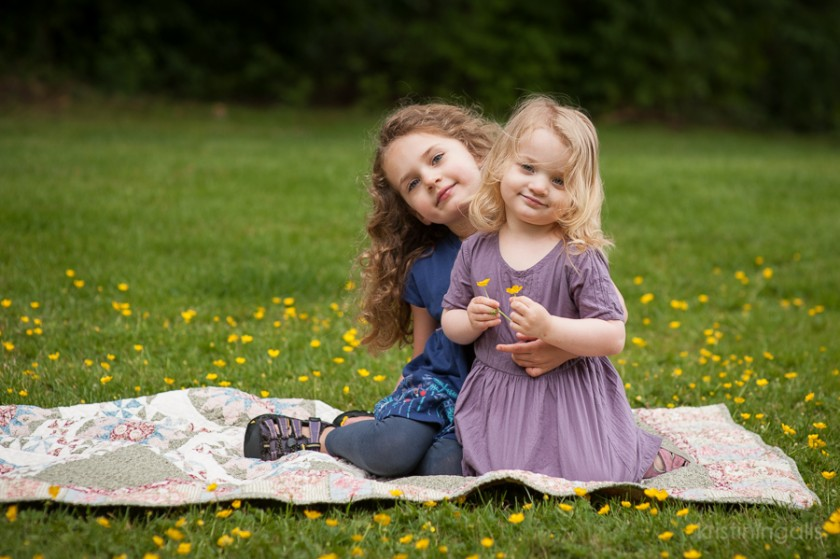sisters sitting on a blanket in a field of flowers photograph by Kristin Ingalls