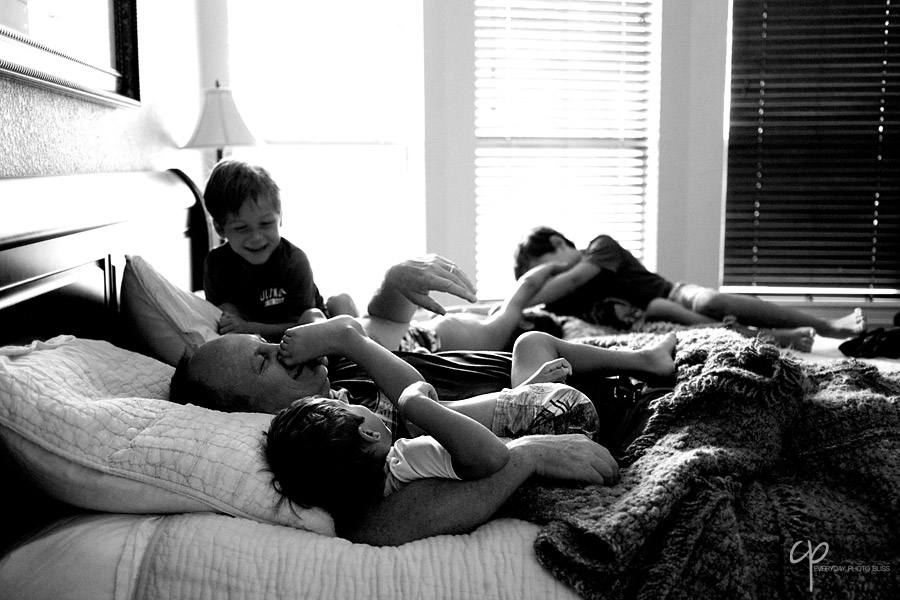 boys playing on bed with their dad photo by Celeste Pavlik