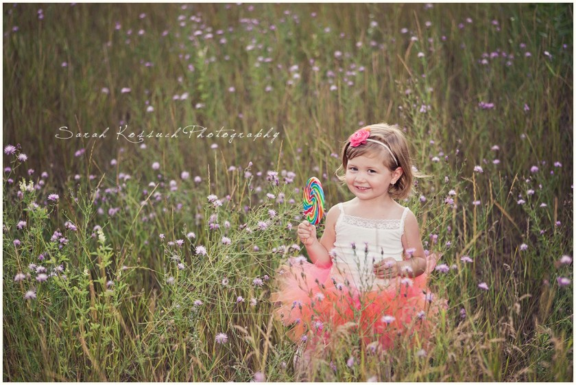 girl in a field with a giant lollipop photo by Sarah Kossuch