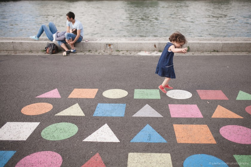little girl jumping by the Seine by Juliette Fradin