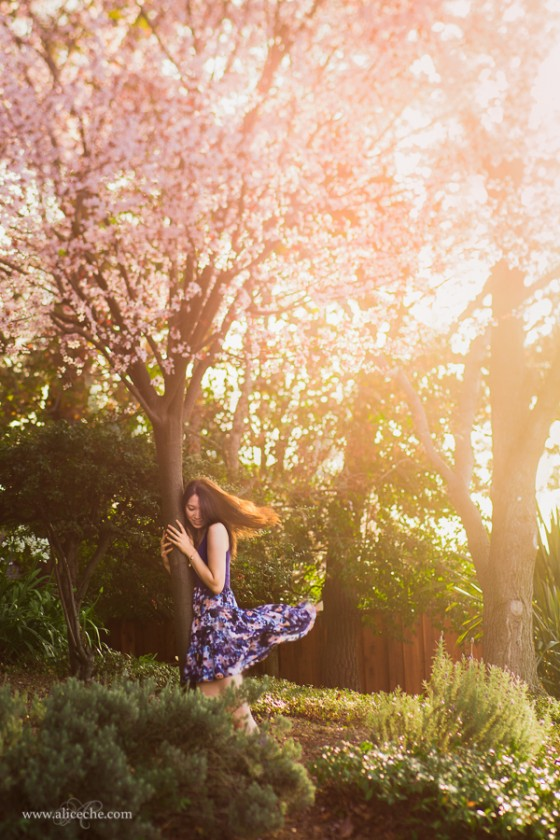 woman holding onto tree with pink blossoms photo by alice che