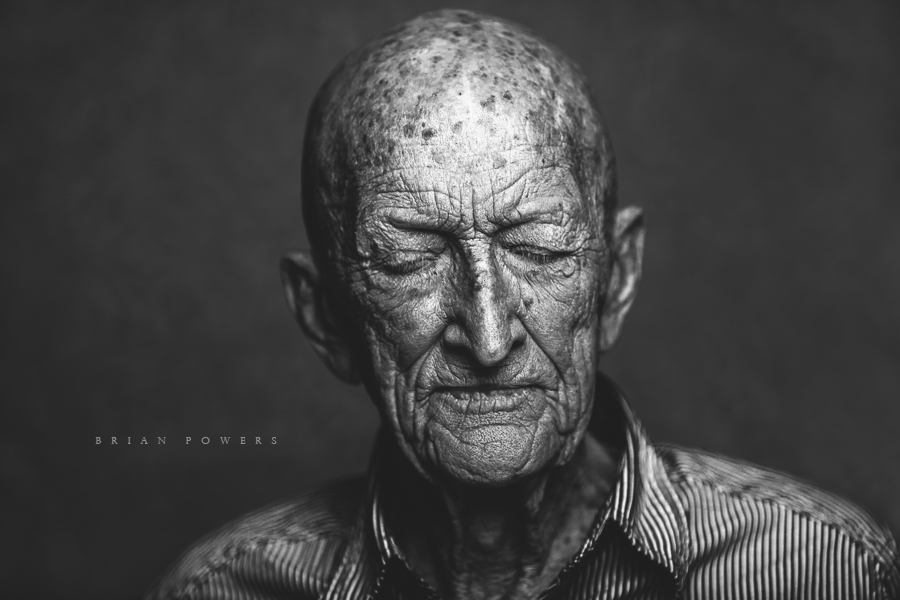 black and white portrait of man with his eyes closed by Brian Powers