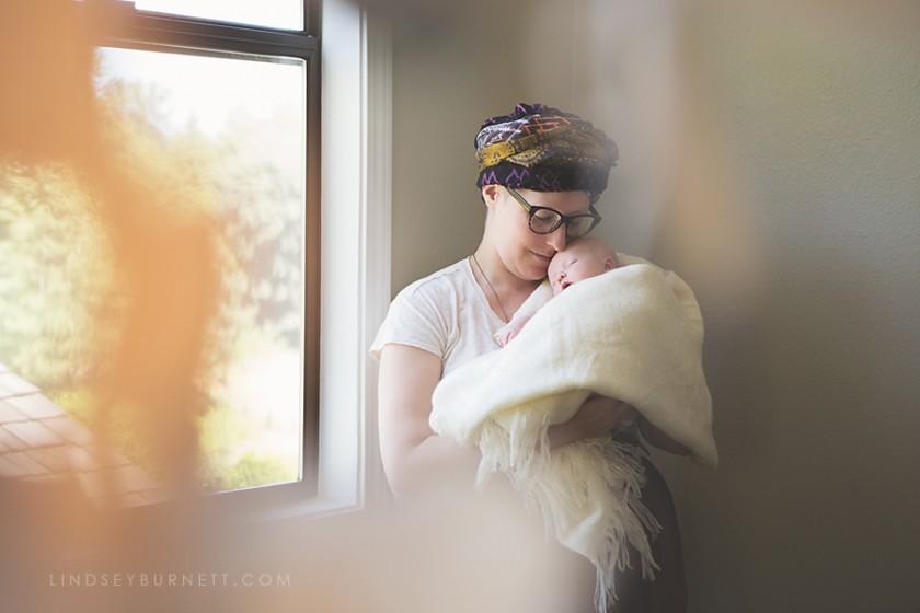 lifestyle photo of mom holding baby by Lindsey Burnett