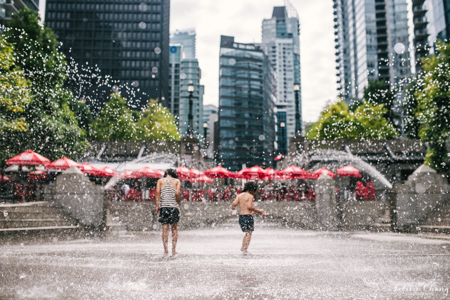 sisters playing in water sprinklers in Vancouver by Felicia Chang