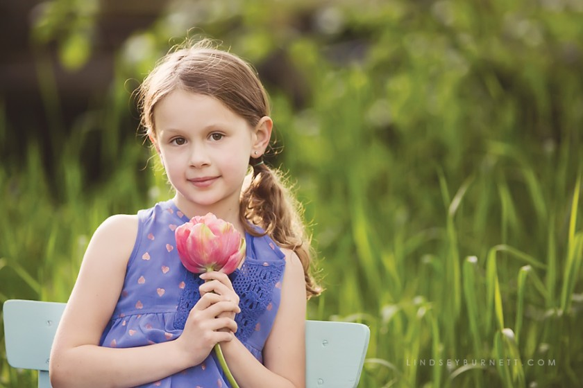 young girl holding a red flower photo by Lindsey Burnett
