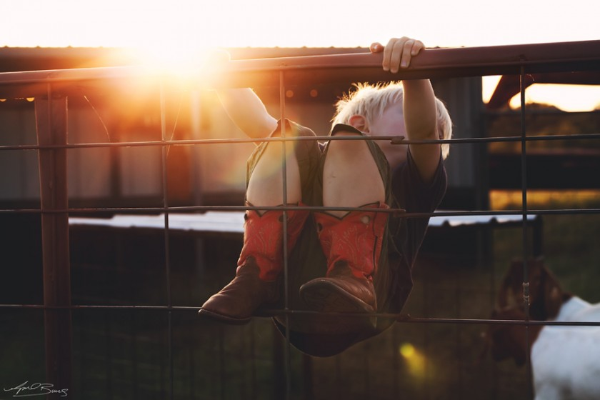 boy hanging on a fence photo by April Burns