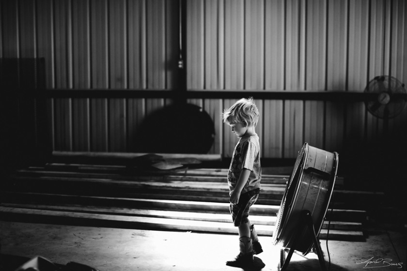 boy standing in front of fan photo by April Burns