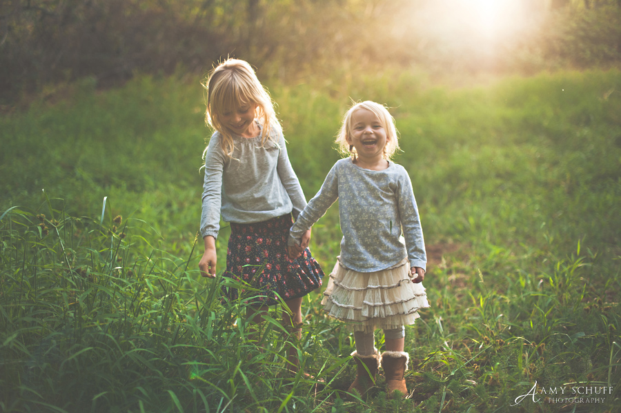 backlit photos of two girls laughing by Amy Schuff