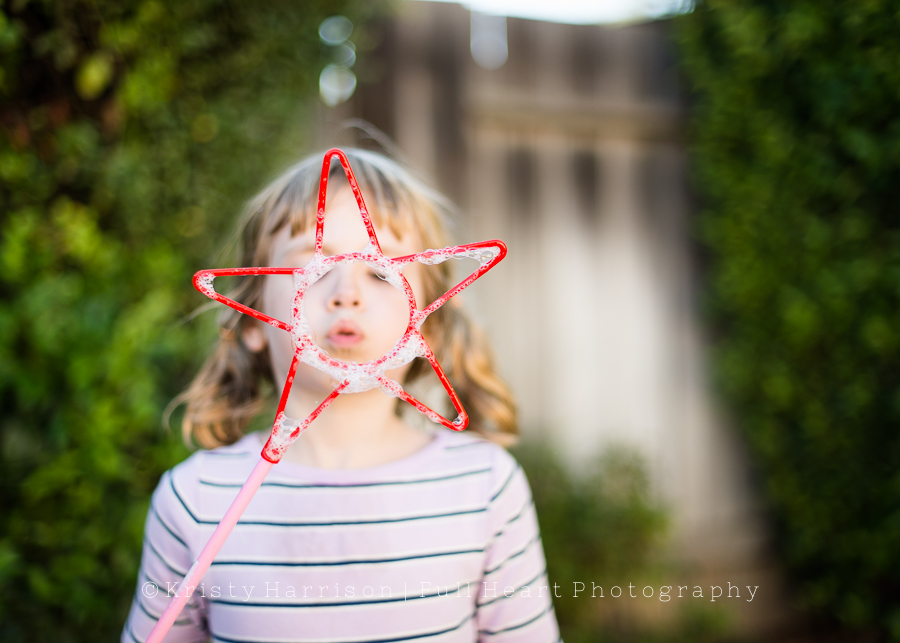 fun photo of child blowing bubbles by Kristy Harrison