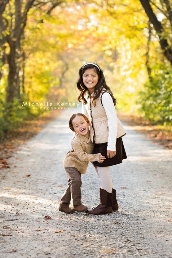 smiling brother and sister on a road by Michelle Kersey