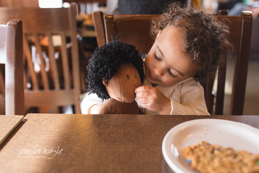 toddler girl feeding doll by Jennifer Bogle