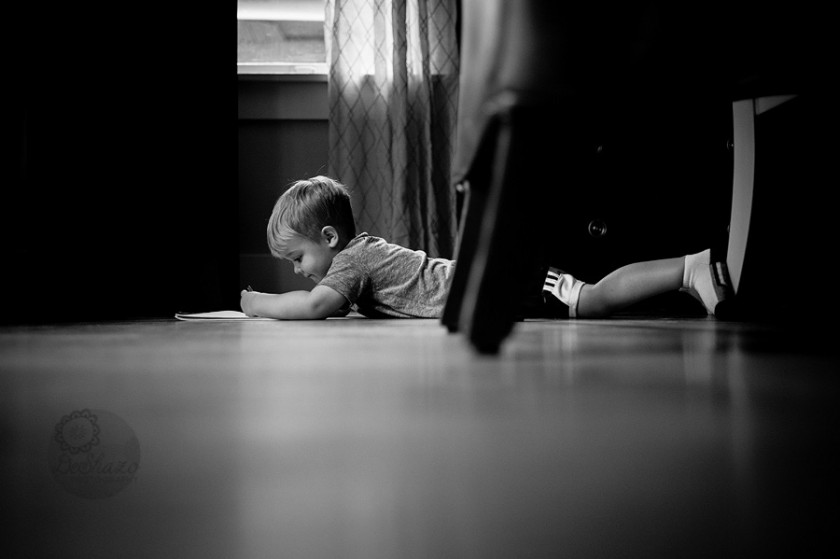 black and white photo of boy laying on floor coloring by Megan DeShazo