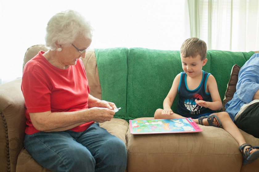 boy and grandma putting a puzzle together by Megan DeShazo
