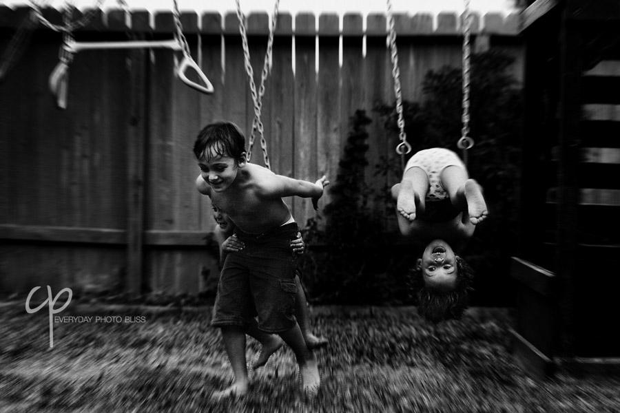 brothers playing on a swingset by Celeste Pavlik