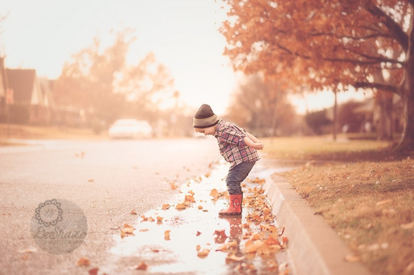 kid jumping in water puddles in street by Megan DeShazo