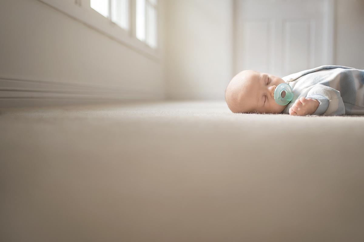 picture of newborn sleeping in sunlight by Kellie Bieser
