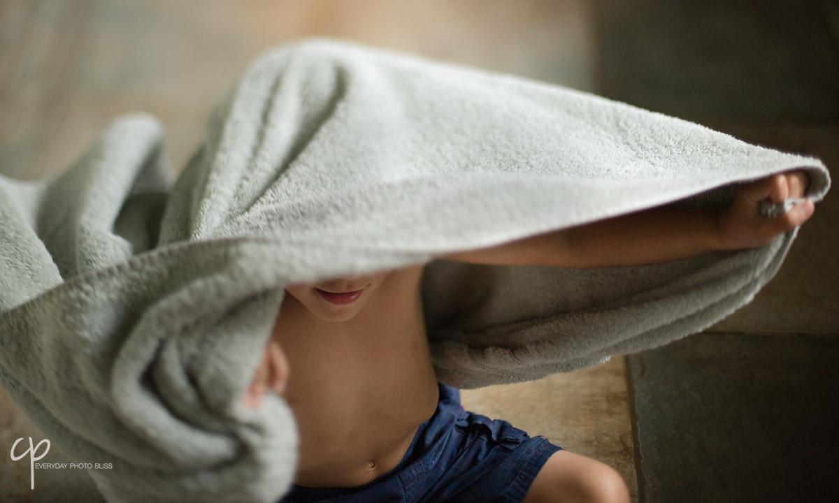 boy playing under a towel by Celeste Pavlik