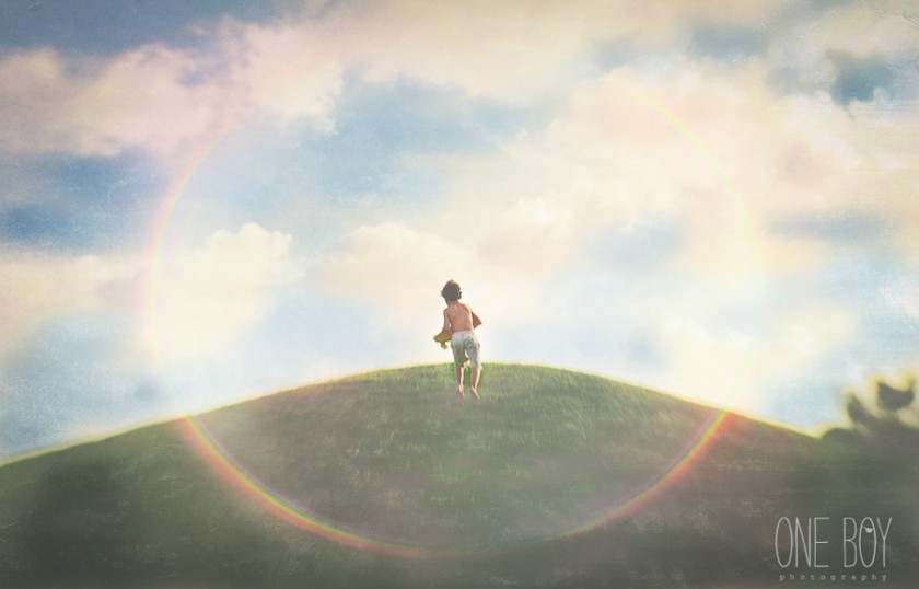 boy running to the top of a hill with sunflare by Jan Tyler