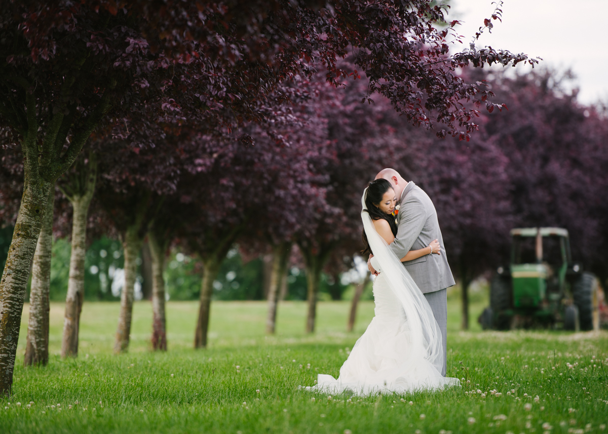 bride and groom portrait in a field with purple trees by Chloe Ramirez