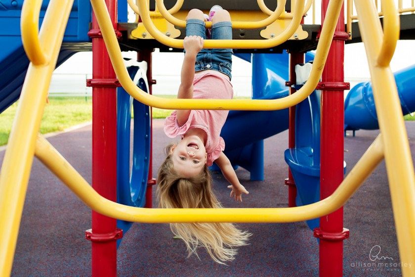 girl playing on playground by Allison McSorley